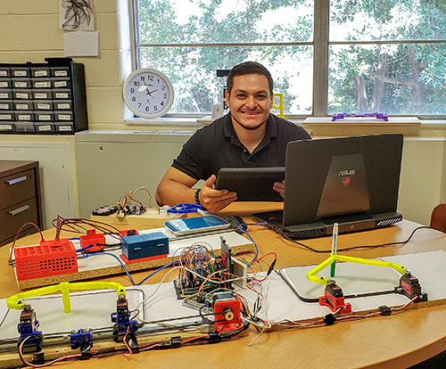 Martin Garcia posing with his engineering project.